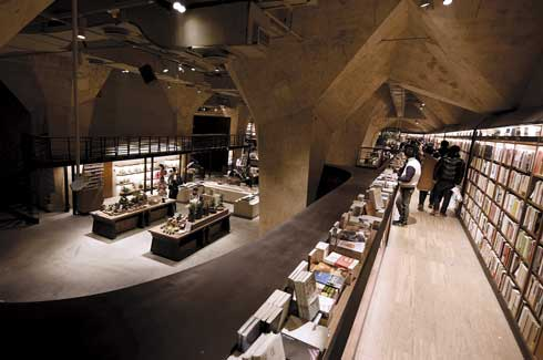 Raw materials and techniques used for a cosmic effect include installing concrete columns, bookcases kept in a loft and ramps across the bookcases.