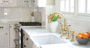White subway tiles and a rustic farmhouse sink overlooked byan un-lacquerred Easton brass faucet set the tone here